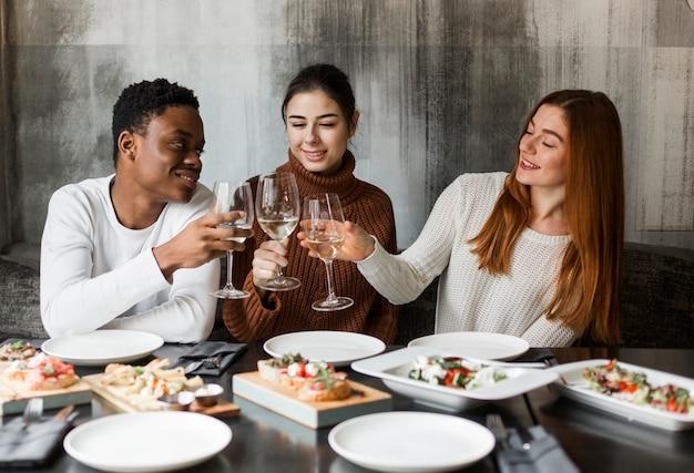 Grupo de jóvenes tomando vino juntos