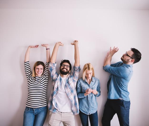 Grupo de jóvenes trabajadores que se apoyan contra la pared como levantar algo mientras uno de ellos mira las uñas.