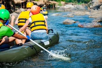 El grupo de jóvenes está transportando en balsa en un río.