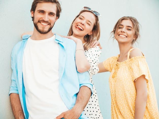 Grupo de jóvenes tres elegantes amigos posando en la calle. hombre de moda y dos chicas lindas vestidas con ropa casual de verano. modelos sonrientes divirtiéndose cerca de la pared. mujeres alegres y chico al aire libre
