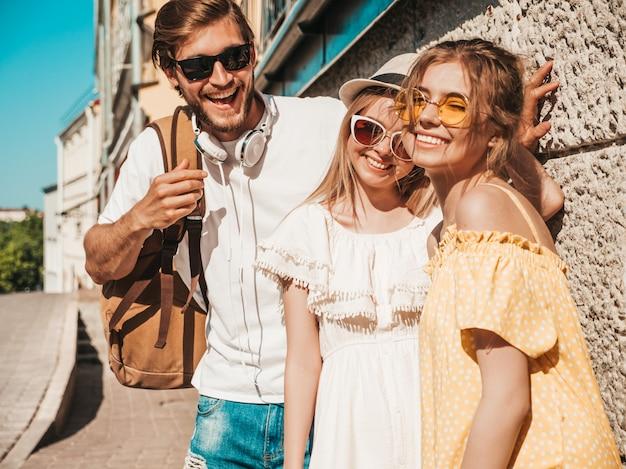 Grupo de jóvenes tres elegantes amigos posando en la calle. hombre de moda y dos chicas lindas vestidas con ropa casual de verano. modelos sonrientes divirtiéndose en gafas de sol. mujeres alegres y chico al aire libre