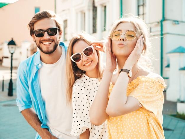 Grupo de jóvenes tres elegantes amigos posando en la calle. hombre de moda y dos chicas lindas vestidas con ropa casual de verano. modelos sonrientes divirtiéndose en gafas de sol. mujeres alegres y chico en susnet