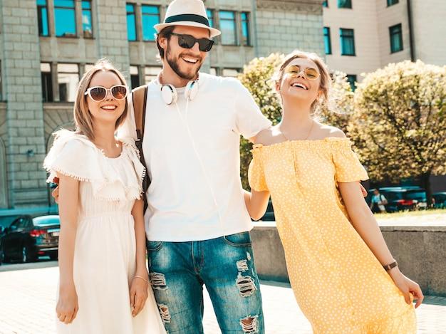 Grupo de jóvenes tres elegantes amigos posando en la calle. hombre de moda y dos chicas lindas vestidas con ropa casual de verano. modelos sonrientes divirtiéndose en gafas de sol. mujeres alegres y un chico volviéndose loco
