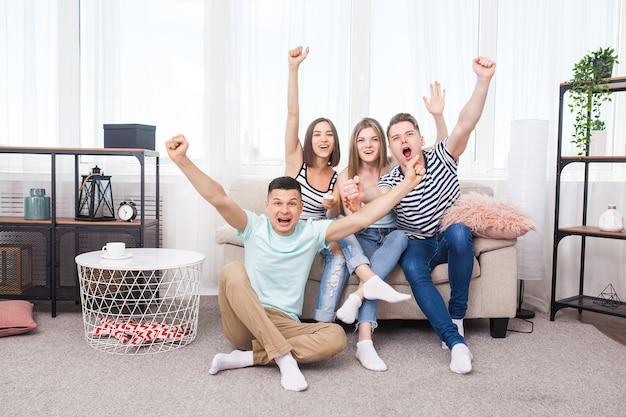 Grupo de jóvenes viendo la televisión. jóvenes activos en casa animando al equipo. alegres amigos en el interior divirtiéndose juntos.