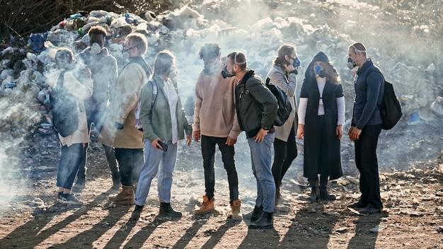 Grupo de jóvenes voluntarios con máscaras antigás cuidan el medio ambiente mientras se paran en el basurero dumpac ...