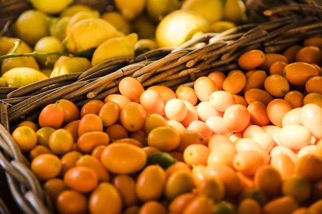Grupo de kumquat en cesta de mimbre en el mercado de frutas