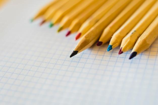Grupo de lápices dispuestos en papel cuadriculado.
