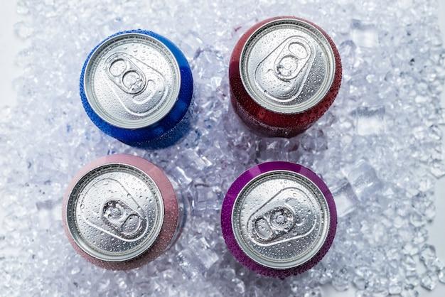 Grupo de latas de aluminio en hielo, bebida fría.