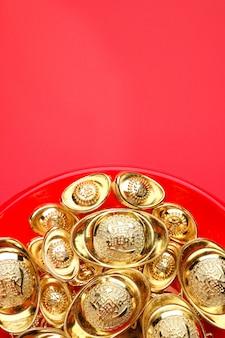 Grupo de lingotes dorados en bandeja roja en fondo rojo. idioma chino en lingotes significa riqueza