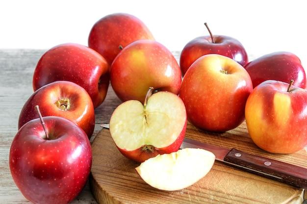Grupo de manzanas rojas frescas, enteras y en rodajas, sobre la placa de cocina de madera y sobre el fondo natural de madera rústica.