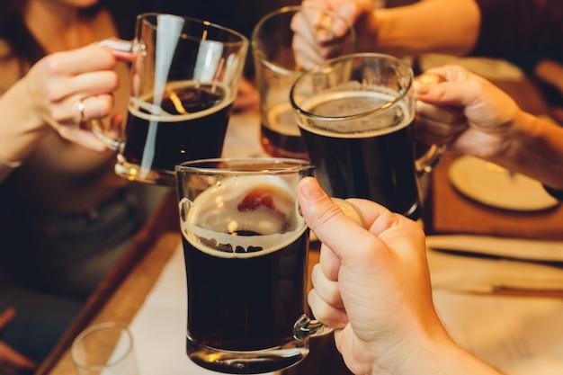 Grupo masculino tintineo vasos de cerveza oscura y ligera en la mesa.