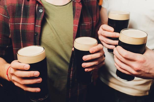 Grupo masculino tintineo de vasos de cerveza oscura y ligera en la pared de ladrillo
