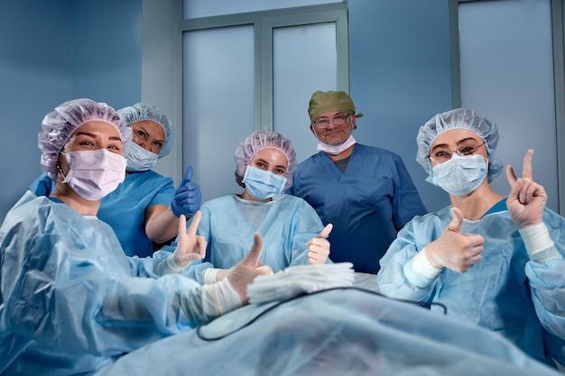 Grupo de médicos cirujanos profesionales sobre el espacio de la clínica en la sala de opacidad sonriendo mirando a la cámara mostrando éxito, signo de pulgares arriba