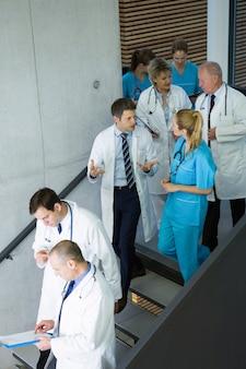 Grupo de médicos y cirujanos que interactúan entre sí en la escalera