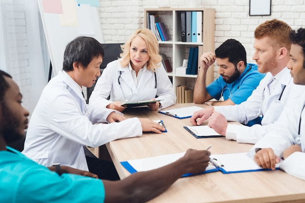 Grupo de médicos de diferentes razas se reúne en una mesa.