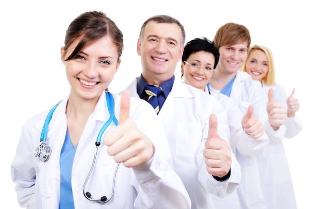Grupo de médicos felices riendo con gesto pulgar hacia arriba de pie en línea