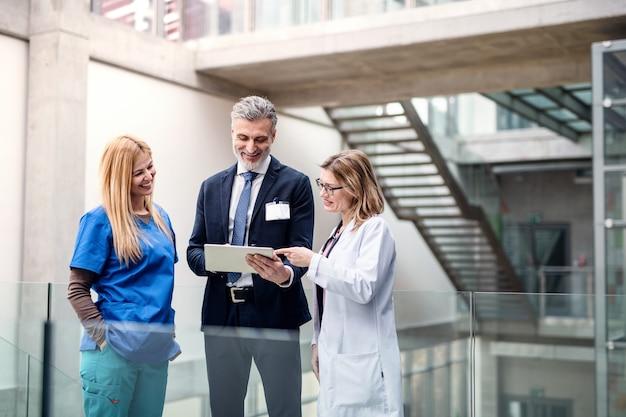 Grupo de médicos hablando con el representante de ventas farmacéuticas en la conferencia.