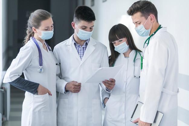 Grupo de médicos en máscaras leyendo papel