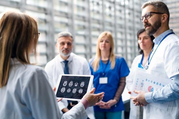 Grupo de médicos con pie de tableta en conferencia médica, discutiendo cuestiones.