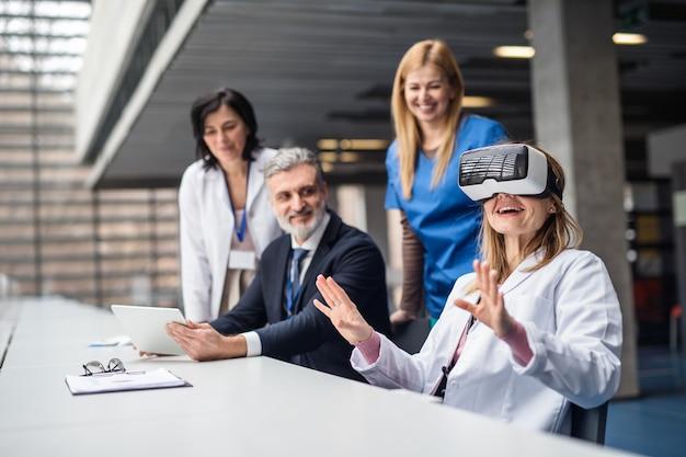 Grupo de médicos y representante de ventas farmacéuticas con gafas de realidad virtual.