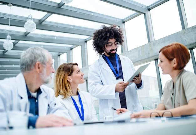 Un grupo de médicos con tableta en conferencia, equipo médico discutiendo problemas.