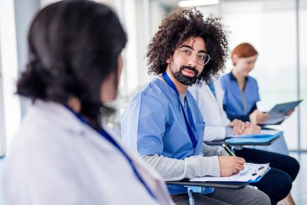 Grupo de médicos con tableta en conferencia médica, sentado y hablando.