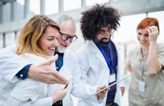 Grupo de médicos con tableta de pie en el pasillo en conferencia médica, hablando.