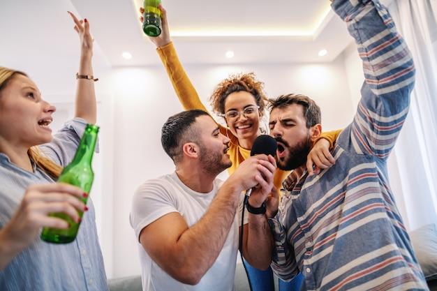Grupo de mejores amigos que se divierten en casa. están bebiendo cerveza y tienen una noche de karaoke.