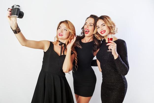 Grupo de mejores amigos, tres chicas elegantes en vestido de lujo negro haciendo autorretrato, bebiendo vino tinto, posando sobre fondo blanco.