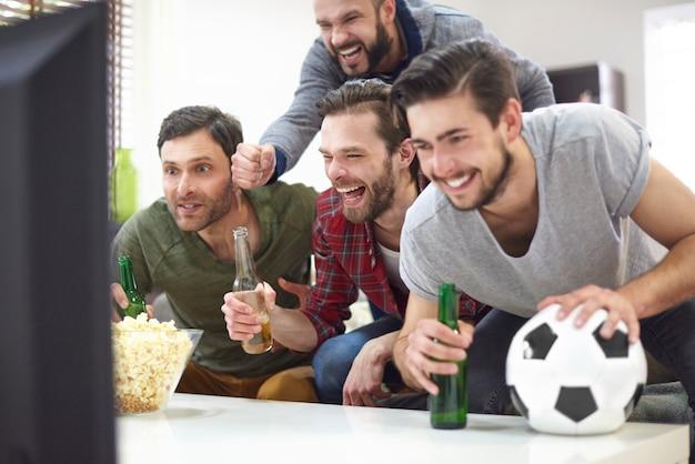 Grupo de mejores amigos viendo partido en la televisión