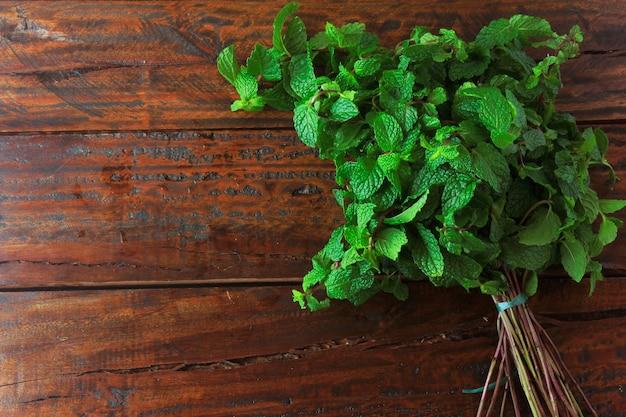 Grupo de menta verde orgánica fresca en mesa de madera rústica
