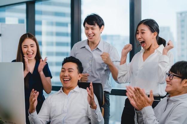 Grupo milenario de jóvenes empresarios asia empresario y empresaria celebran dando cinco después de tratar de sentirse feliz y firmar un contrato o acuerdo en la sala de reuniones en la pequeña oficina moderna.