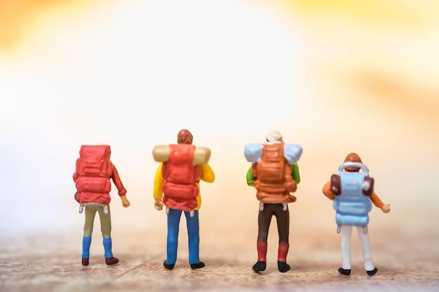 Grupo de mini figuras de viajeros con mochila de pie en el mapa