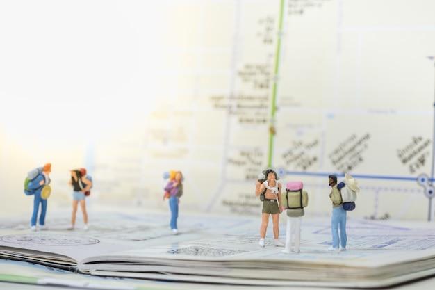 Grupo de mini figuras de viajeros con mochila de pie.