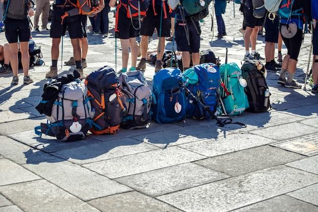 Grupo de mochila de peregrino en una fila de adoquines de la plaza obradoiro, santiago de compostela, españa