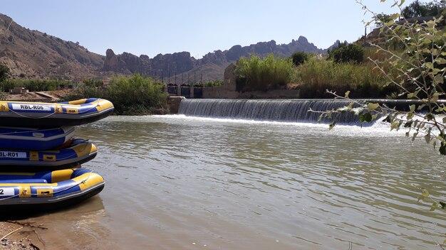 Grupo de muchas personas practicando rafting en un río tranquilo en grandes botes inflables