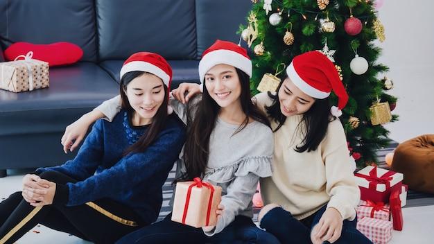 Grupo de mujer hermosa asiática con cajas de regalo. cara sonriente en la habitación con decoración de árboles de navidad