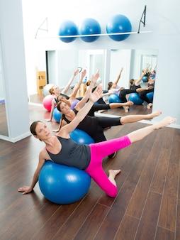 Grupo de mujeres aeróbicas pilates con balón de estabilidad.
