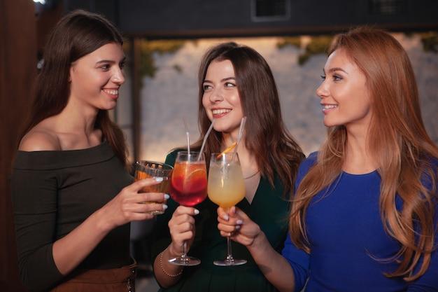 Grupo de mujeres alegres celebrando en el bar, tomando cócteles juntos