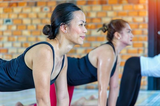 Grupo de mujeres asiáticas haciendo yoga namaste plantean