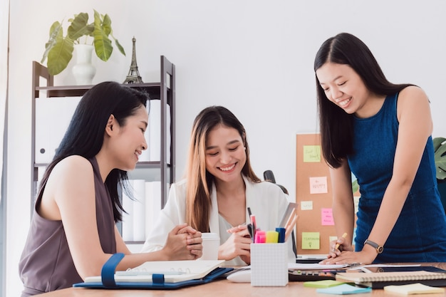 Grupo de mujeres asiáticas hermosas que se encuentran en oficina para discutir negocio.