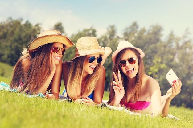 Un grupo de mujeres en bikini tomando selfie al aire libre