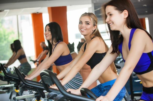 Un grupo de mujeres bonitas en la bicicleta estática sonriendo y entrenando. hermosas chicas alegres en el gimnasio