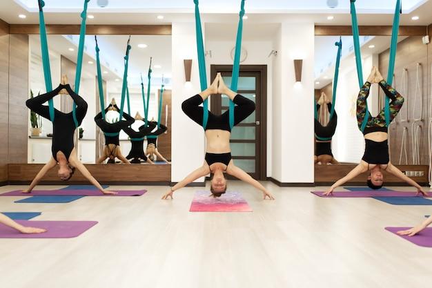 Un grupo de mujeres cuelga boca abajo en una hamaca. volar clase de yoga en el gimnasio