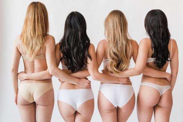 Grupo de mujeres delgadas en ropa interior de pie en abrazo