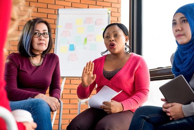Grupo de mujeres diversas discutiendo en la reunión.