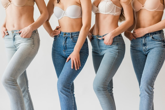 Grupo de mujeres diversas posando en sujetadores y jeans.