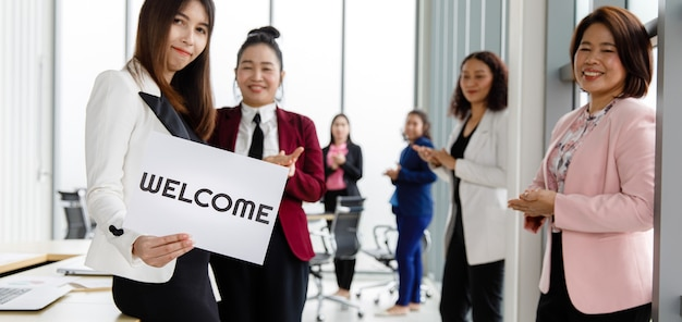 Grupo de mujeres empresarias asiáticas se une a saludar y mantener palabras de bienvenida en señal de felicidad y placer por venir de algo o alguien.