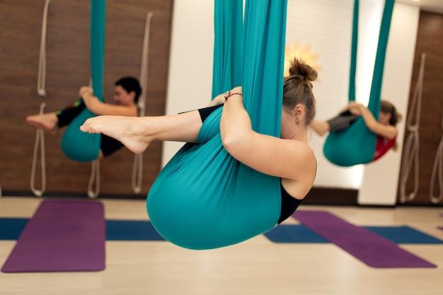 Un grupo de mujeres están colgadas en posición fetal en una hamaca. clase de yoga con mosca en el gimnasio