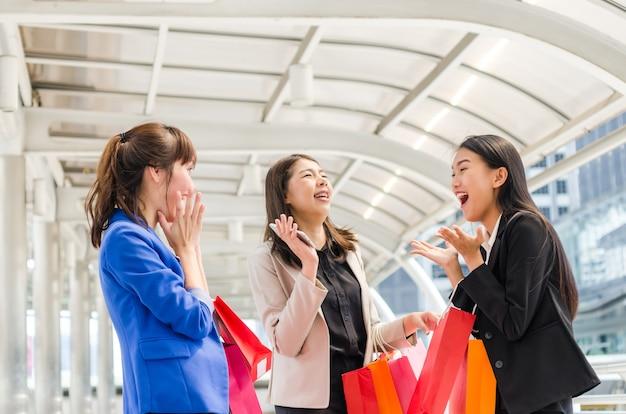 Grupo de mujeres felices de asia que hacen compras con los bolsos de compras.